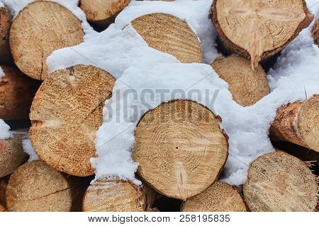 Pile Of Firewood Background. Firewood Stacked In A Pile Of Snow On The Street. Winter Weather Is Sno