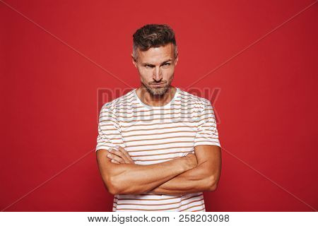 Irritated man 30s in striped t-shirt standing with arms crossed and angry look isolated over red background poster