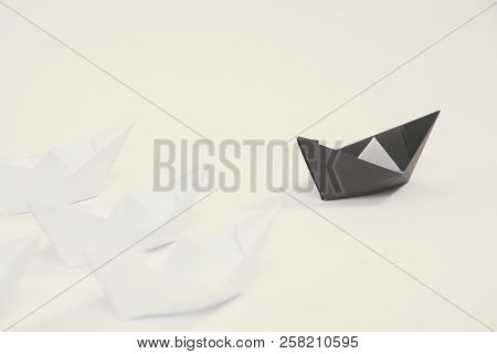 Creative Black Paper Ship Among White. Concept Leadership Different.