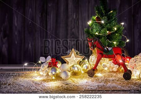 Christmas card with firtree balls and red wooden horse white snow copyspace.