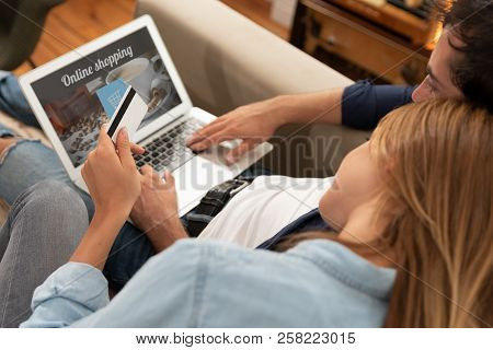 Young Couple Shopping Online And Using A Credit Card