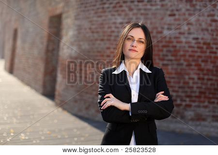 Busineswoman Is Standing In Front Of A Brick Wall