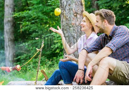 Pleasant smell of roasted food makes picnic atmosphere perfect. Picnic roasting food over fire. Couple in love relaxing sit on log having snacks. Family enjoy weekend in nature. Idyllic picnic date poster