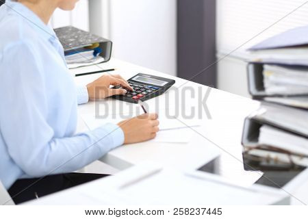 Unknown female bookkeeper or financial inspector calculating or checking balance, making report, close-up. Internal Revenue Service at work with financial document. Tax and audit concept poster