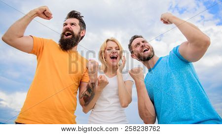 Unbelievable Luck. Threesome Winners Happy With Raised Fists. We Are Winners. Woman And Men Look Emo