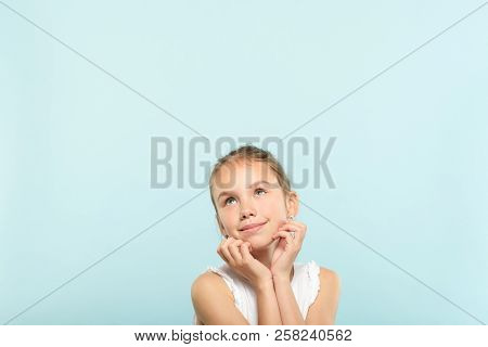 Smiling Cute Pensive Young Girl Looking Up At A Virtual Object Or Text Speech Bubble. Empty Space Fo