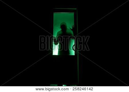 Silhouette Of An Unknown Shadow Figure On A Door Through A Closed Glass Door. The Silhouette Of A Hu