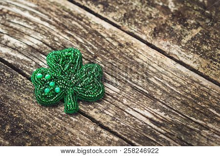 Handmade jewelry, brooch with beads. Jewelry brooch. Woman jewelry. Workshop jewelry, copy space. Brooch clover on rustic wooden background. Three leaf clover brooch. Womens accessories poster