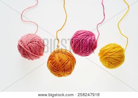Colorful woolen balls over white background. Balls of wool partially unrolled.