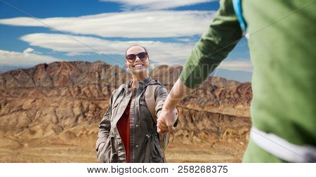 travel, hiking, backpacking, tourism and people concept - happy couple of travelers with backpacks holding hands and walking over grand canyon national park background