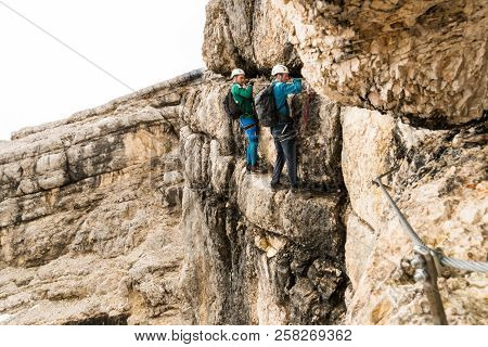 two young male mountain climbers on very exposed Via Ferrata in Alta Badia in the Italian Dolomites poster
