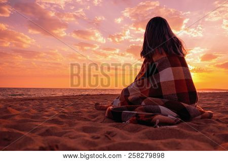 Unrecognizable Young Woman Relaxing On Sand Beach Near The Sea At Sunset.