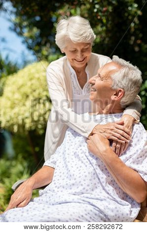 Senior woman hugging man in medical cloth in the hospital garden. Loving wife embracing old hospitalized husband outdoors. Caring wife supporting husband in illness in a private medical clinic.