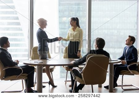 Smiling Multiracial Business People At Meeting Shaking Hands