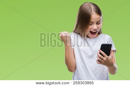 Young beautiful girl sending message texting using smarpthone over isolated background screaming proud and celebrating victory and success very excited, cheering emotion