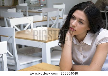 Portrait Of Good-looking Pensive Brunette Sitting At Work And Dreaming Looking Faraway. Cute Young W