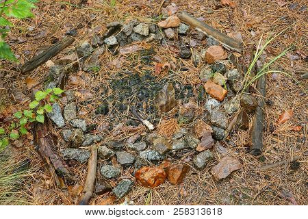 Extinct Fire With Black Ash And Wet Stones In The Forest