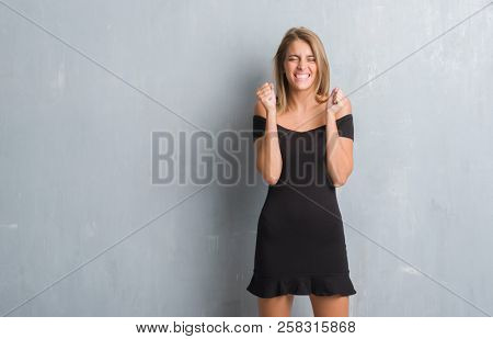 Beautiful young woman standing over grunge grey wall wearing elegant dress excited for success with arms raised celebrating victory smiling. Winner concept.