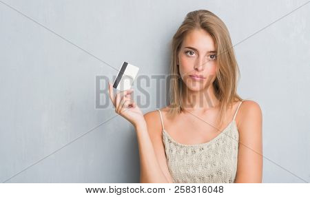 Beautiful young woman over grunge grey wall holding credit card with a confident expression on smart face thinking serious