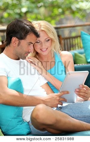 Couple relaxing in sofa with electronic tablet
