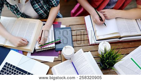 Young Couple With Books And Notes In Cafe. Smart Young Guy And Girl In University Campus. Learning A