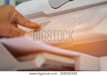 Business Documents Concept : Businesswoman Hands Working In Process Press Of Paper In Laser Printer