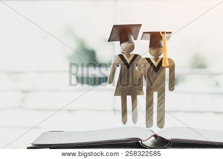 Back To School Concept, Two People Sign Wood With Graduation Celebrating Cap On Open Textbook Show A