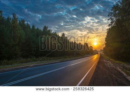 Asphalt Road In The Rays Of The Rising Sun.