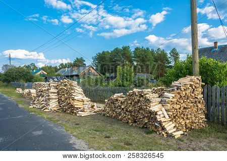 A Large Pile Of Firewood On A Village Street.