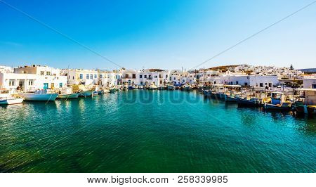 Fishboats and yachts moored in Naoussa port, Paros island, Greece. View on dock for boats and yachts at bright sunny day