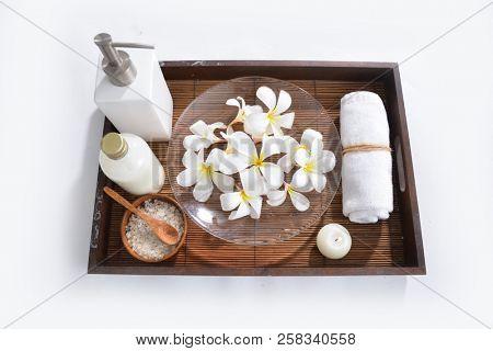 Many white frangipani in bowl ,bottle oil, candle, towel, salt in bowl on basket