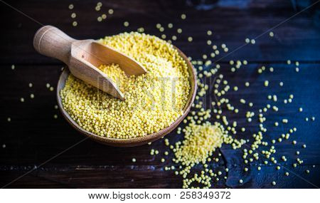 Organic Raw Millet Seeds In A Rustic Bowl On Wooden Table With Copyspace