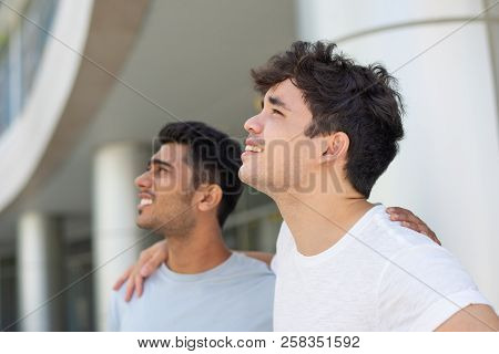 Portrait Of Cheerful Male Friends Embracing And Looking Up Outdoors. Young Indian And Hispanic Male