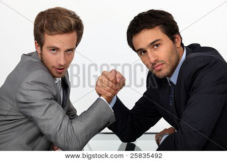 two young men well dressed doing arm-wrest