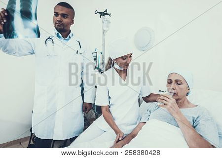 Woman Undergoes Rehabilitation. After Treatment For Cancer. Nurse With Glass Of Water. Doctor Looks