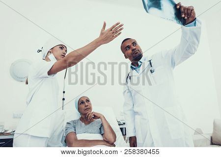 Doctor And Nurse In Ward. Doctor Looks At The X-ray. Woman On The Mend. Woman Undergoes Rehabilitati