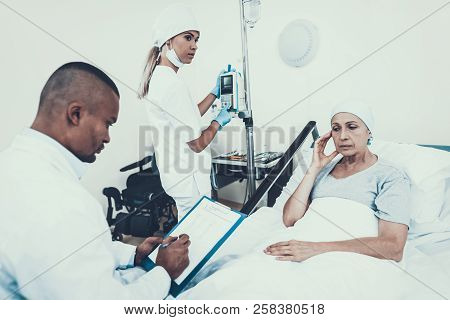 Nurse Puts A Dropper. Cancer Patient. Stethoscope On Neck. Woman On Bunk. Cancer Patient. Nurse With