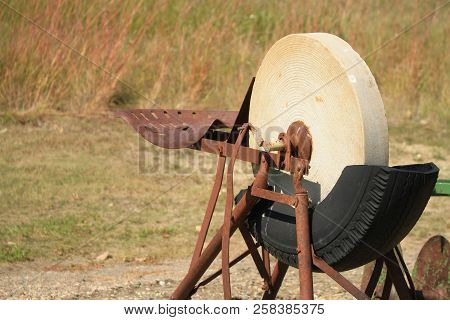 An Antique Pedal Operated Grinding Stone With A Old Tire Filled With Water To Lubricate The Stone,