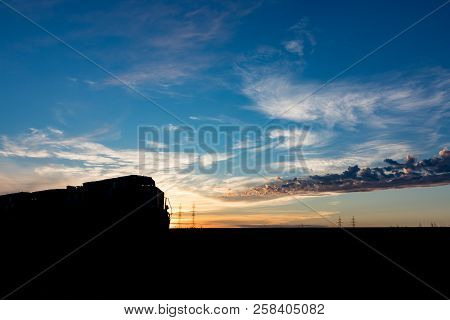 Silhouetted Train At Sunset On The Canadian Prairie