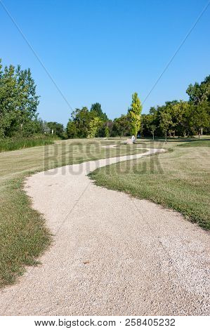 Winding Gravel Path Through Green Parkland Vertical Crop
