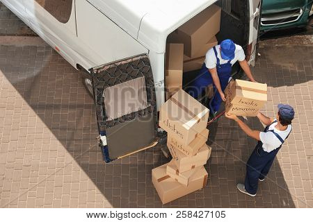 Male Movers Unloading Boxes From Van Outdoors, Above View