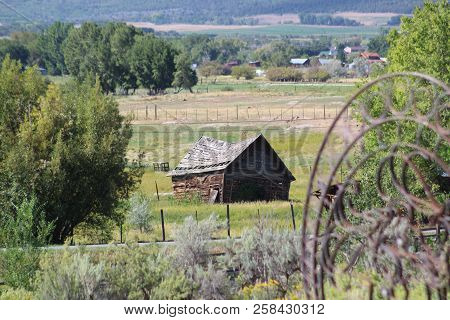 A Weathered Old Barn Slowly Collapses In A Little Valley Behind A Quiet Cemetery In The Colorado Mou