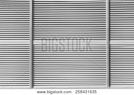 The Texture Of The Shutter Door Or Window In Light Gray Color. Metal Gates Or Shutters For Garage Or