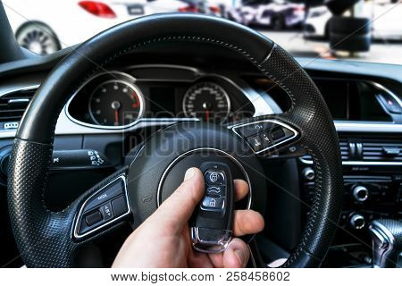 Man's Hand Holding A Wireless Car Key In Black Leather Interior. Modern Car Interior Details. Car De