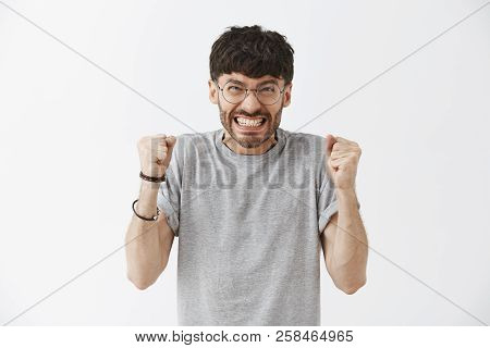 Attractive Bearded Man Clenching Teeth Not To Shout From Rage And Anger Raising Fists And Staring An