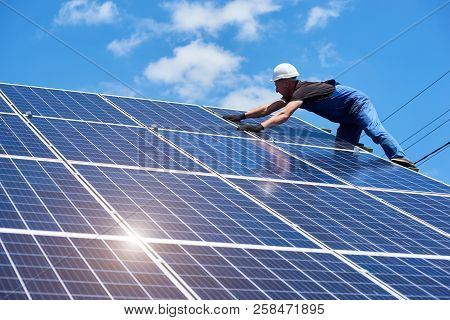 Professional Worker Installing Solar Panels On The Green Metal Construction, Using Different Equipme
