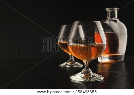 Two Glasses Of Brandy Or Cognac And Bottle On Black Background. Luxury Aperitif At Restaurant, Menu