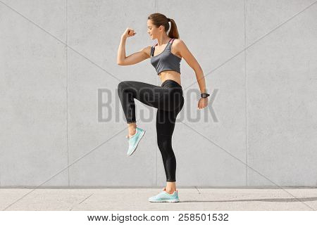 Photo Of Fitness Woman Has Intense Workout, Raises Legs, Dressed In Sportsclothes, Preapres For Runn