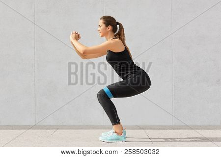 Strong Sporty Caucasian Woman Has Exercises With Rubber Resistance Band, Trains Legs, Works On Muscl