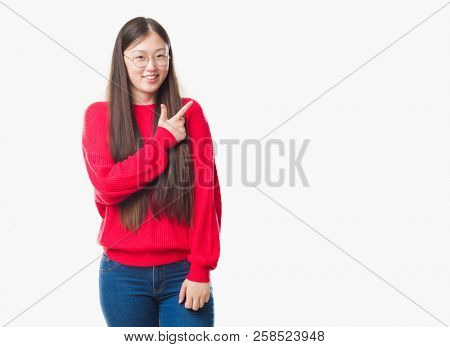 Young Chinese woman over isolated background wearing glasses cheerful with a smile of face pointing with hand and finger up to the side with happy and natural expression on face looking at the camera.